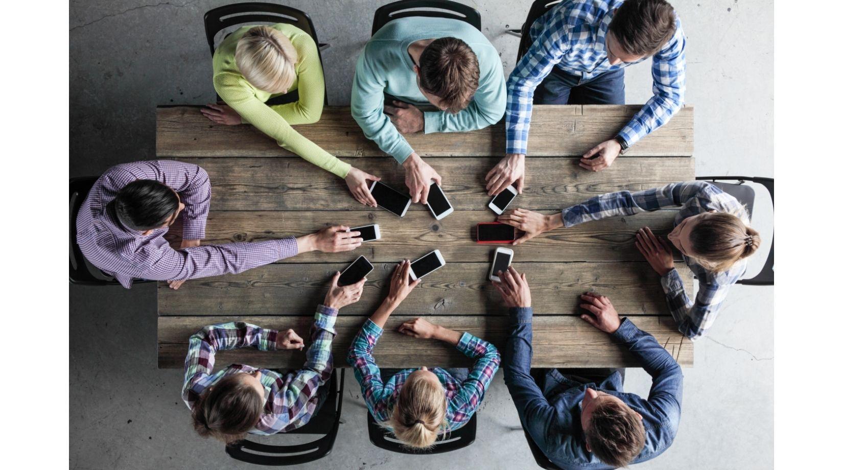 люди за столом с телефонами